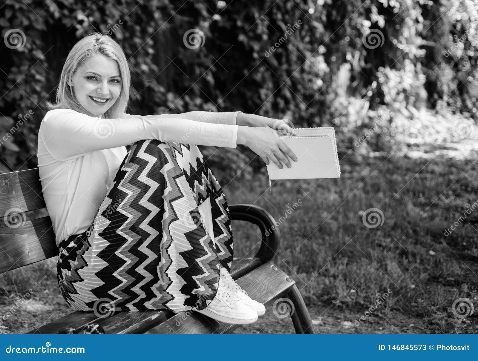 Entspannen Sie sich sogar wenige Minuten verringern Druck Griffbuchgartens Dame sonniger Tag des recht gl?cklichen M?dchen sitzen