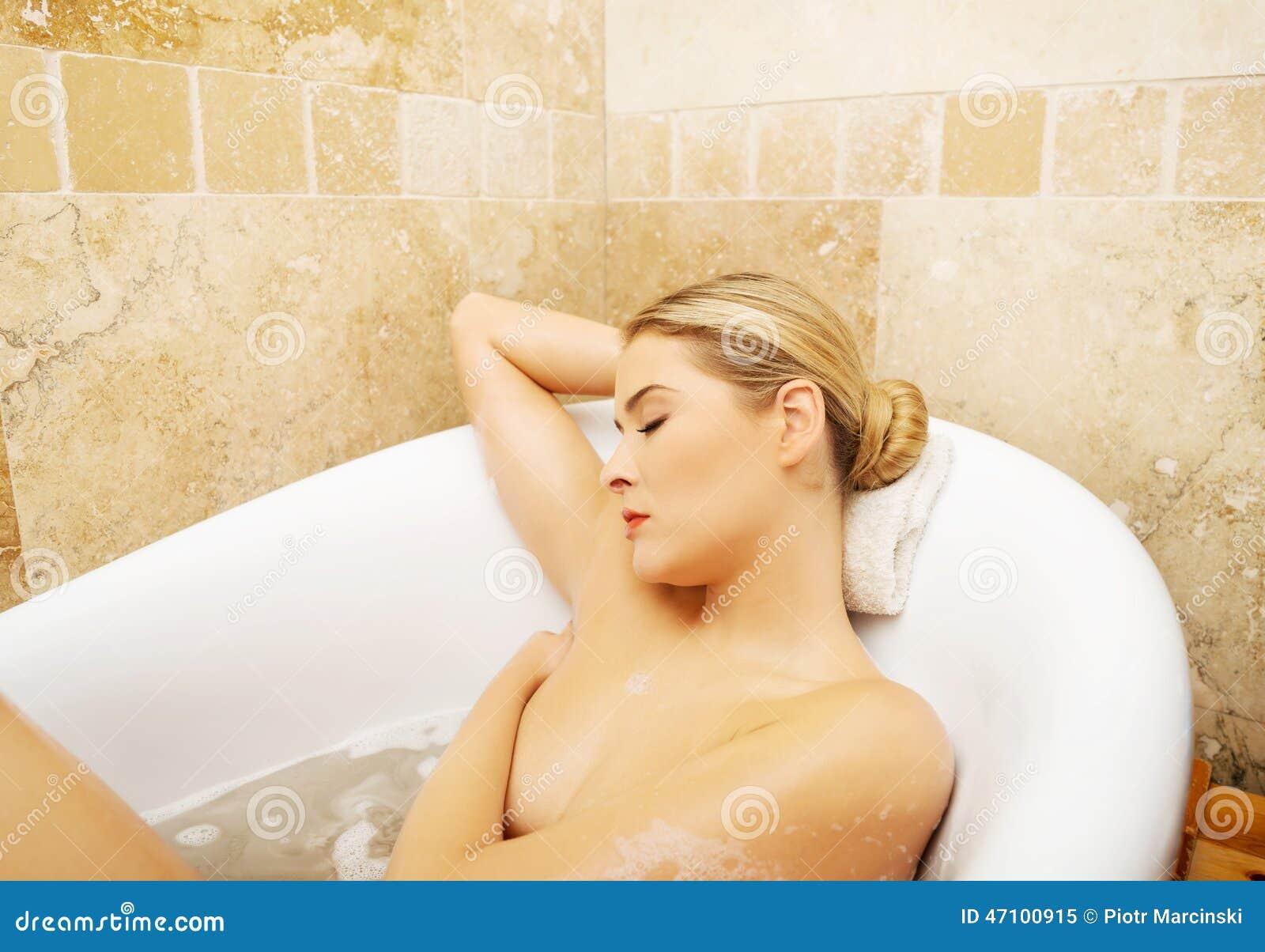 Entspannende Frau, die auf Bad durch Ellbogen sützt