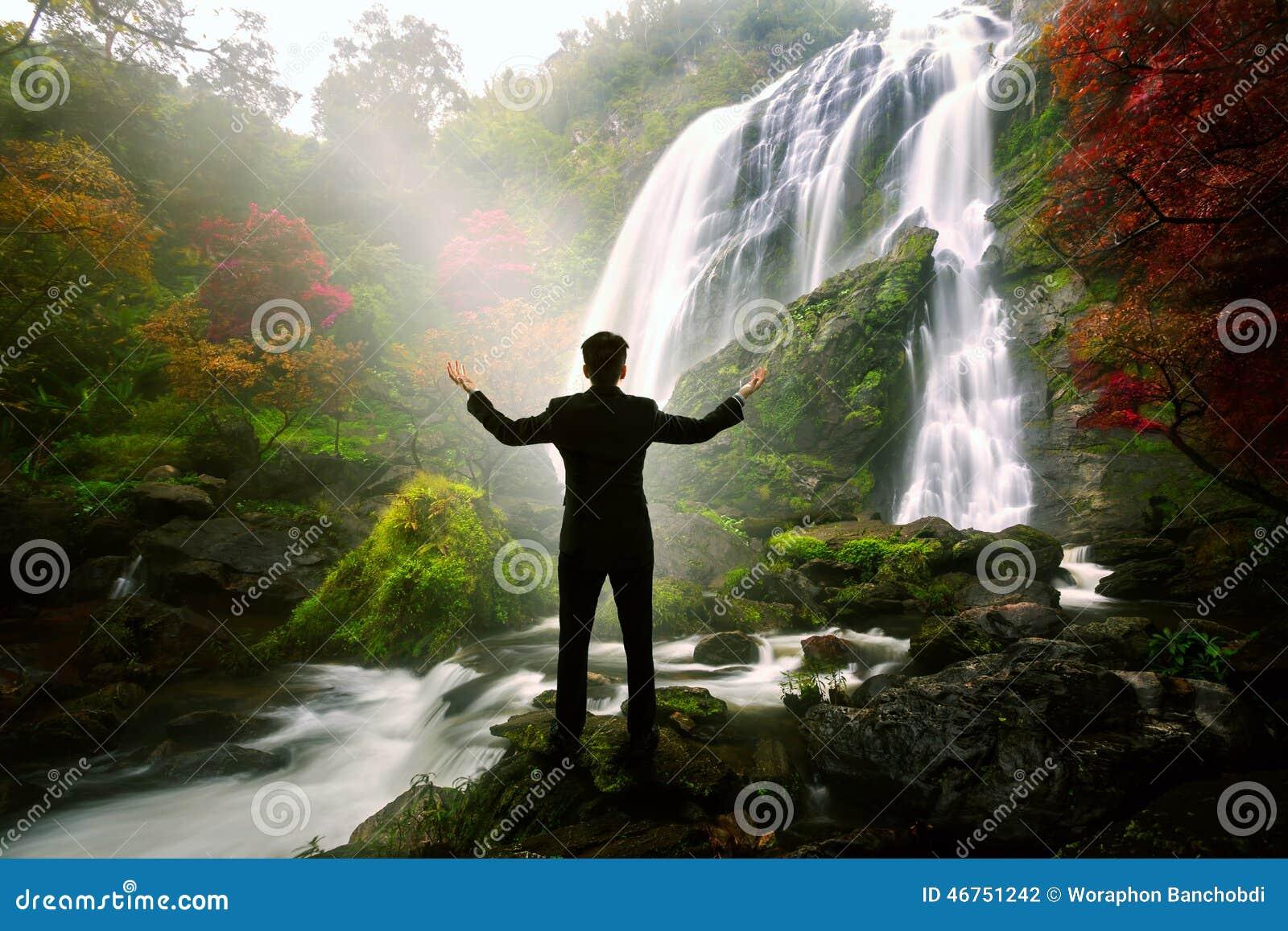 Entspannender Geschäftsmann, der am Wasserfall steht