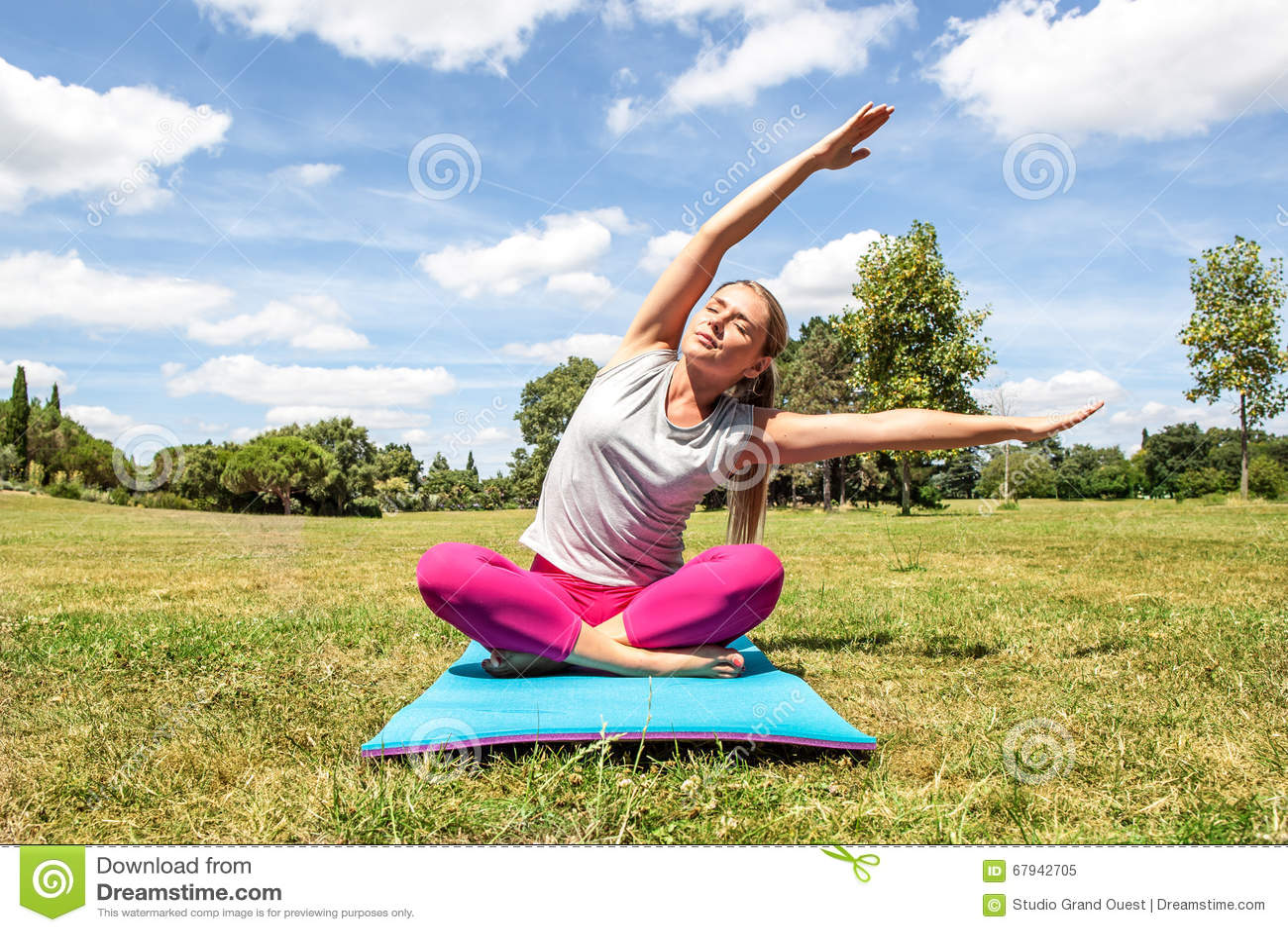 Entspannte blonde Frau, die Yoga mit verbogenem oberem Körper tut