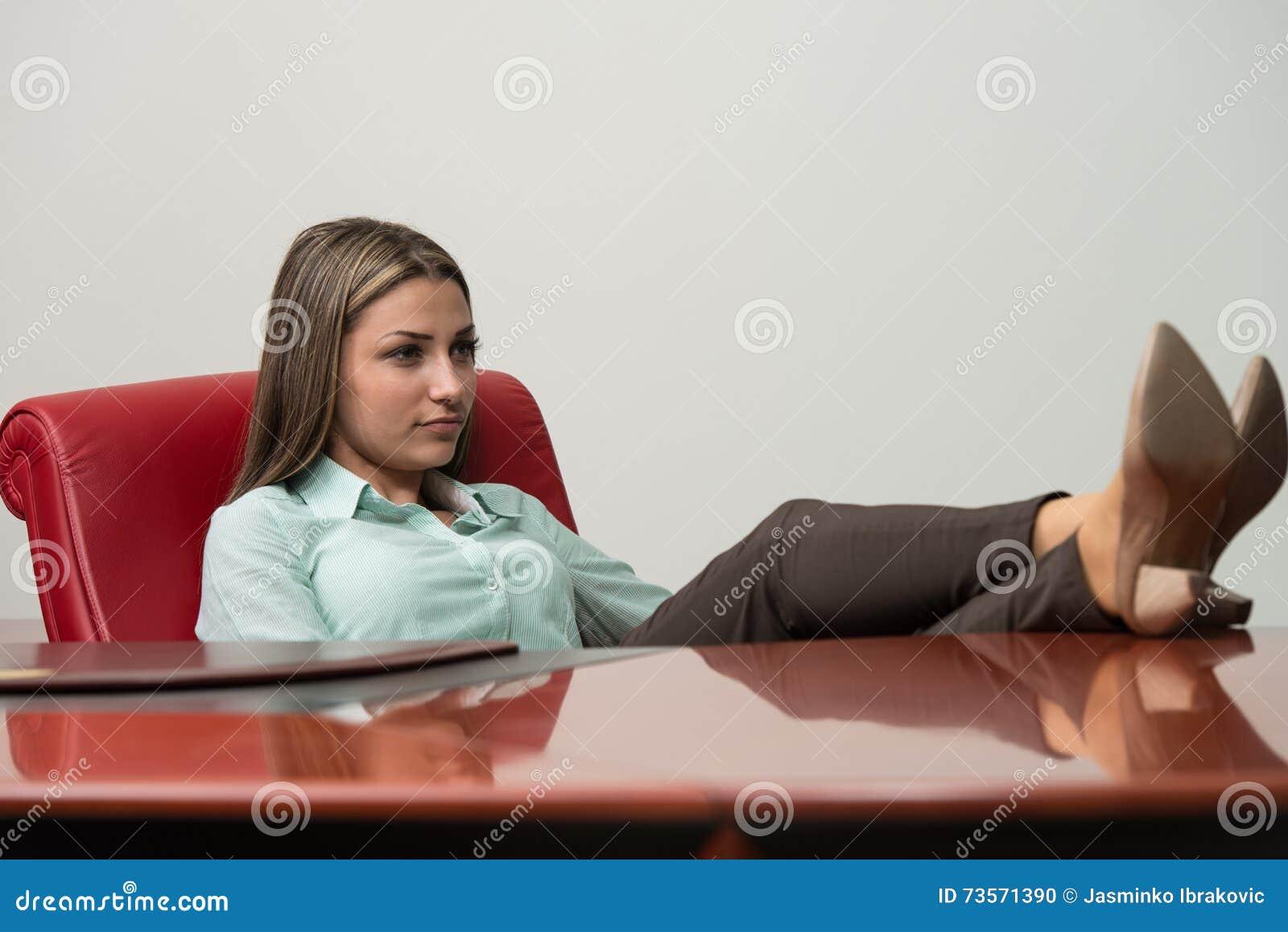Entspannte Geschäftsfrau mit den Beinen auf dem Schreibtisch