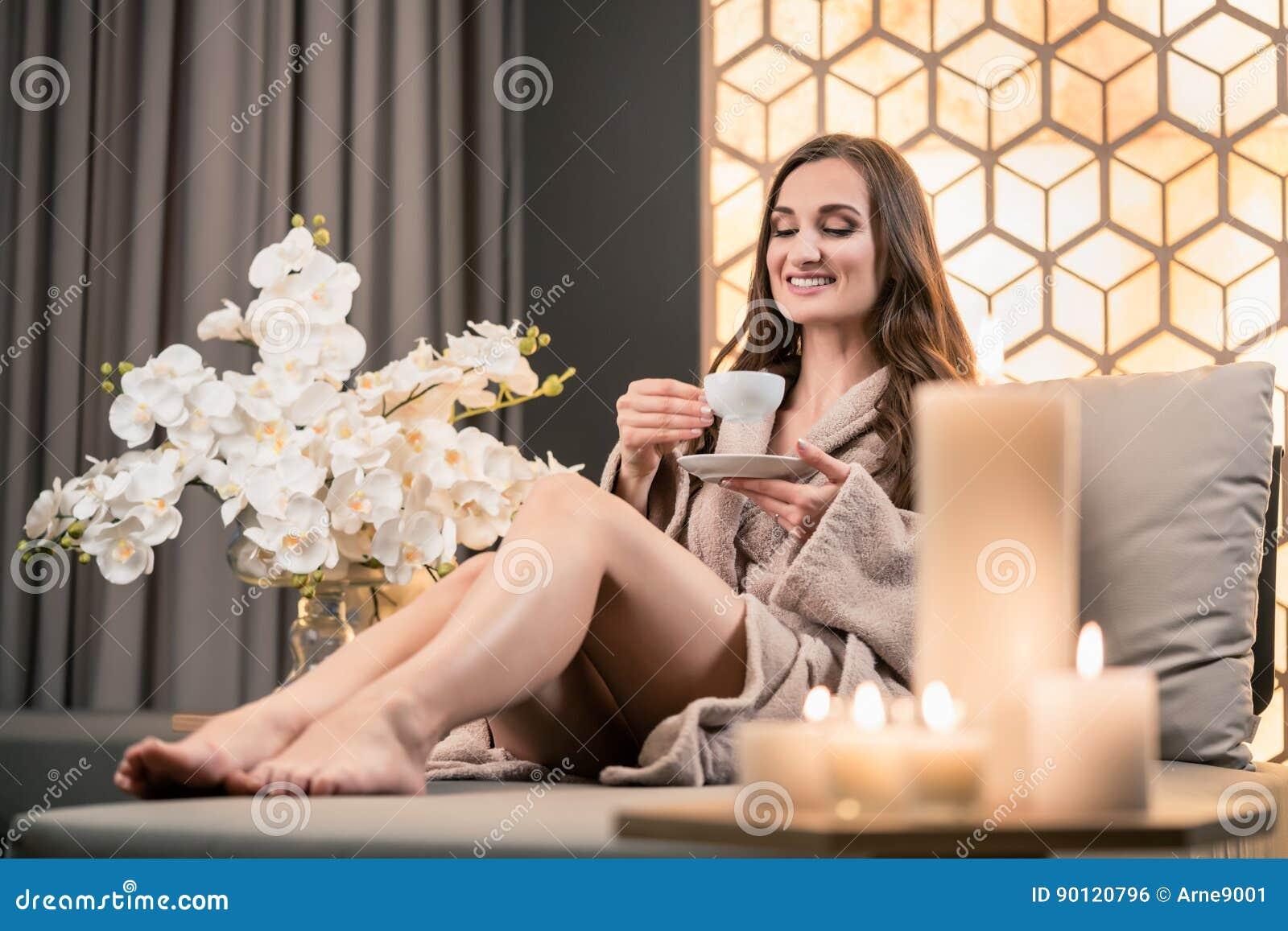 Entspannte junge Frau, die Kräutertee vor Badekur trinkt