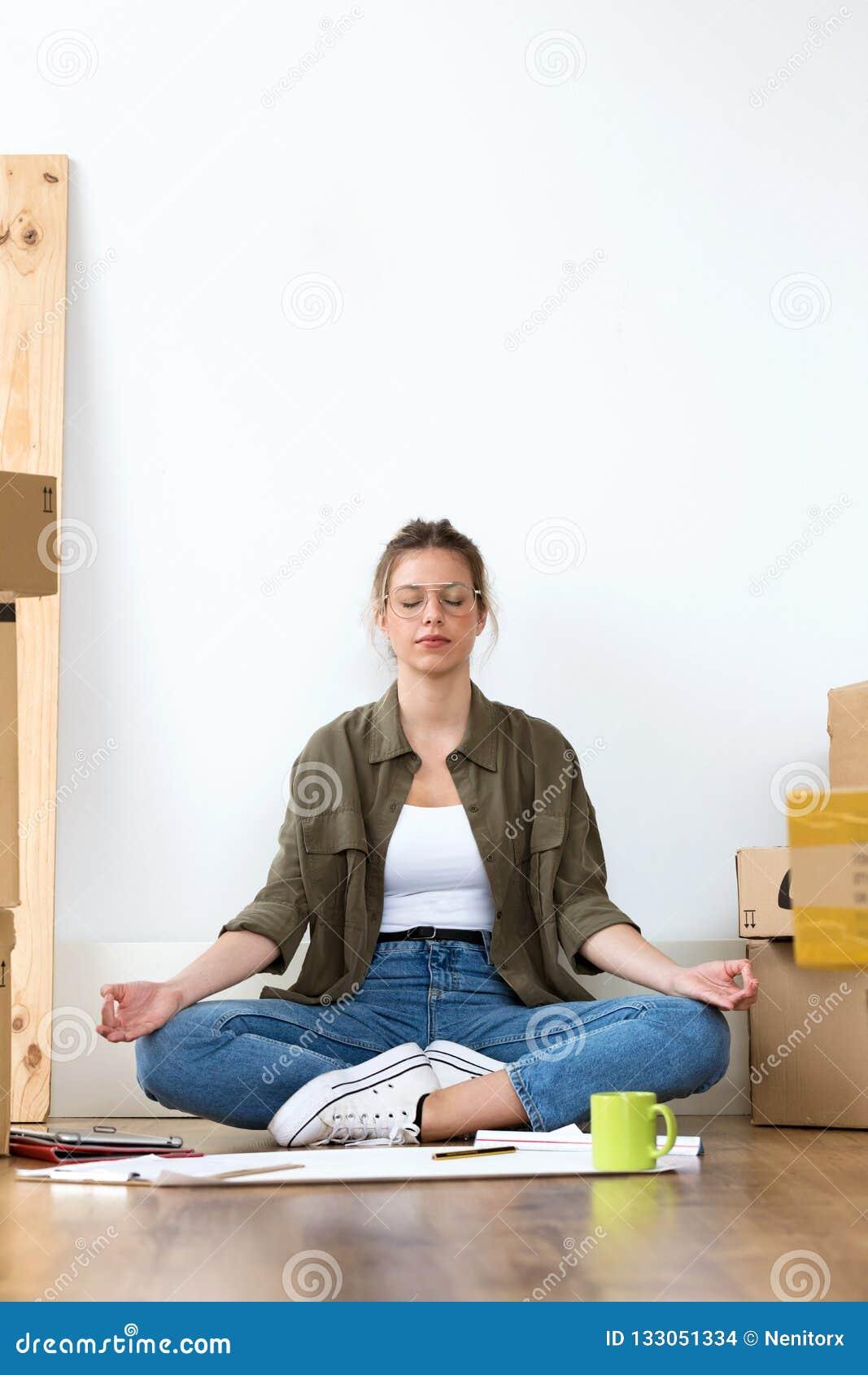 Entspannte junge Frau, die Yoga beim Sitzen auf dem Boden ihres neuen Hauses tut
