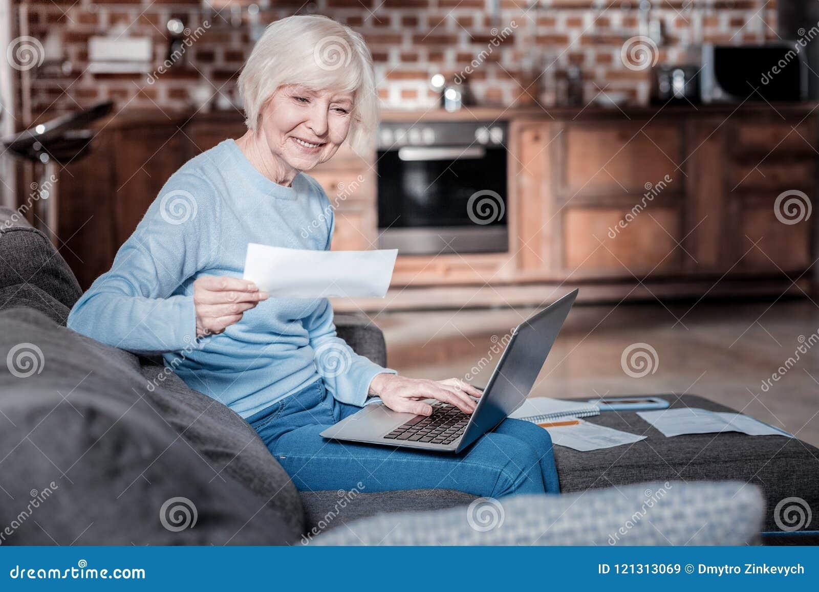 Entspannte reife Frau, die mit Computer arbeitet