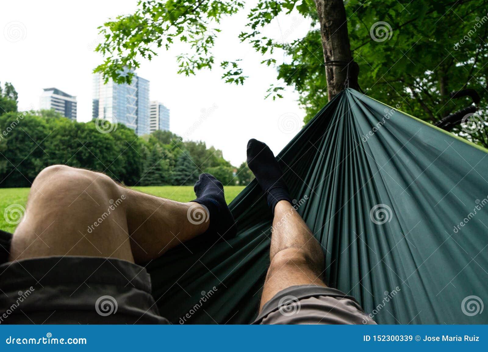 Entspannung in der grünen Hängematte im Sommer in einem Stadtpark Socken in den Füßen schließen oben Gebäude und Grashintergrund
