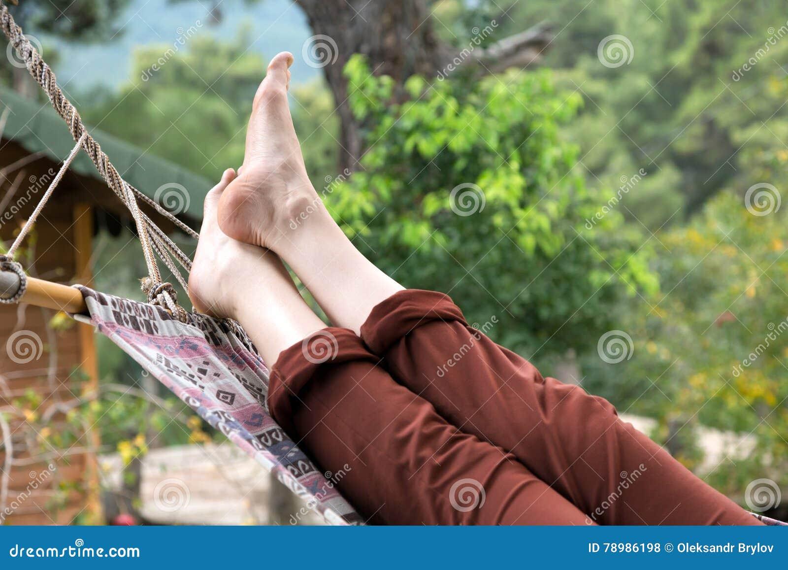 Entspannungslügen der Person in der Hängematte am ländlichen Häuschengarten