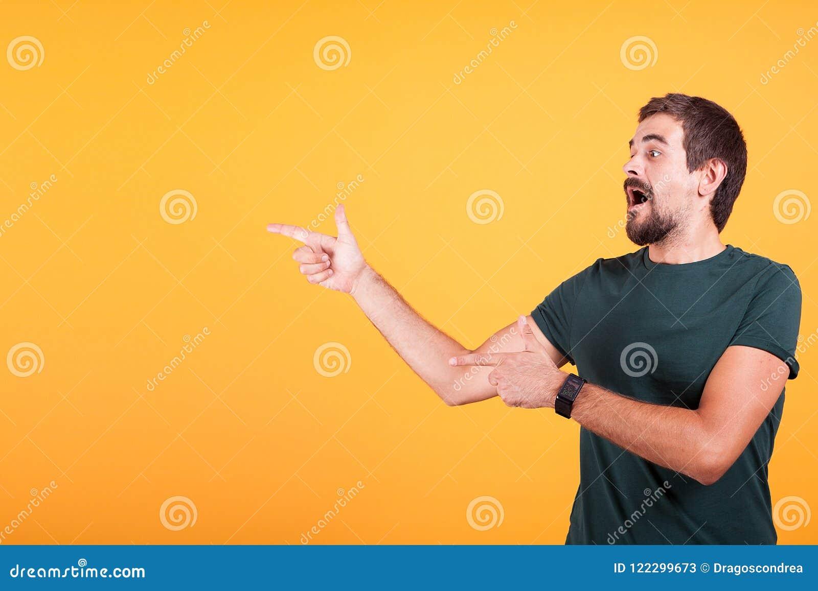 Entusiasmo e homem expressivo que apontam no copyspace