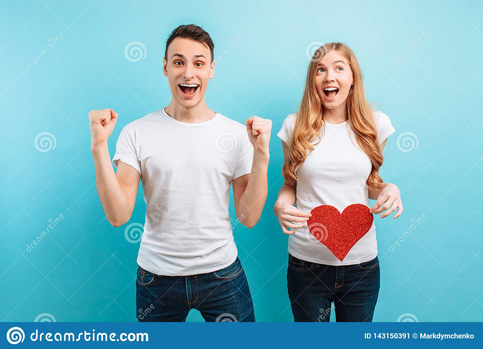 Entusiastisk man som lär om havandeskapet av hans fru, en gravid kvinna som rymmer en röd pappers- hjärta mot buken
