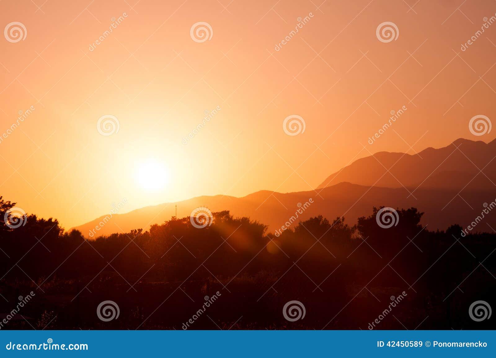 Entwurfsfoto der Sonne einstellend über Berge