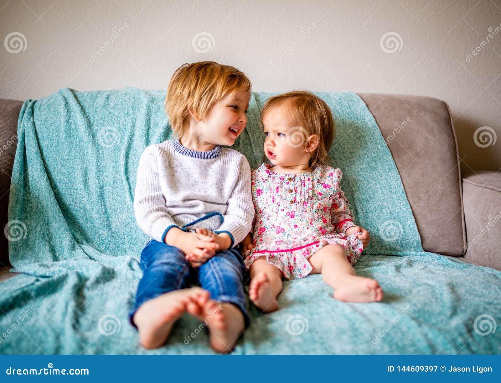 Entzückende Geschwister sitzen auf Couch zusammen