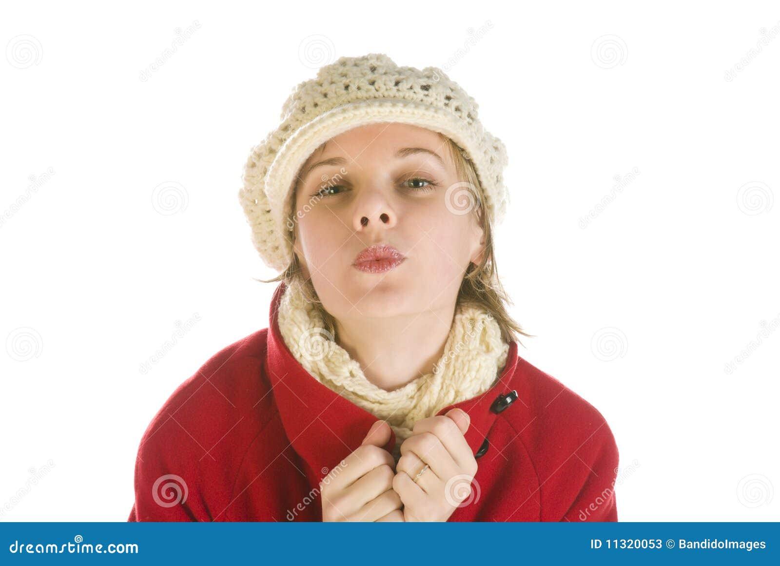 Entzückende junge Frau in einem Winterschutzkappenküssen