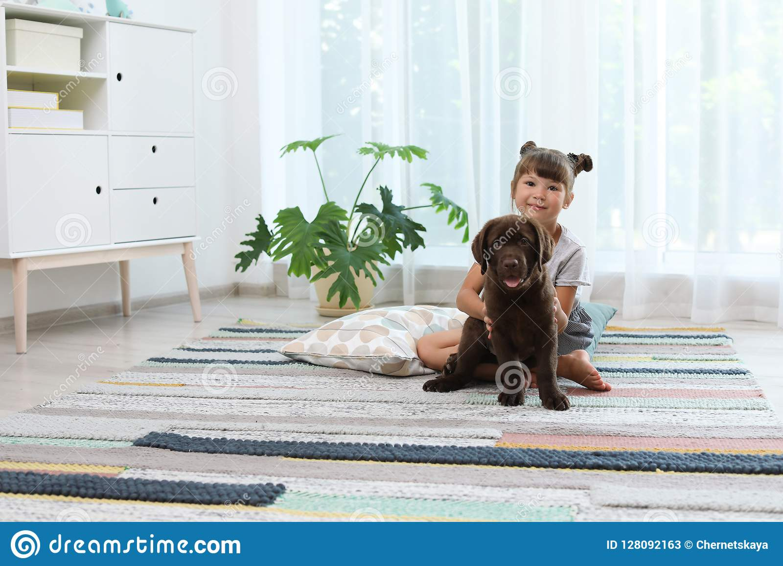 Entzückende Schokolade labrador retriever und kleines Mädchen