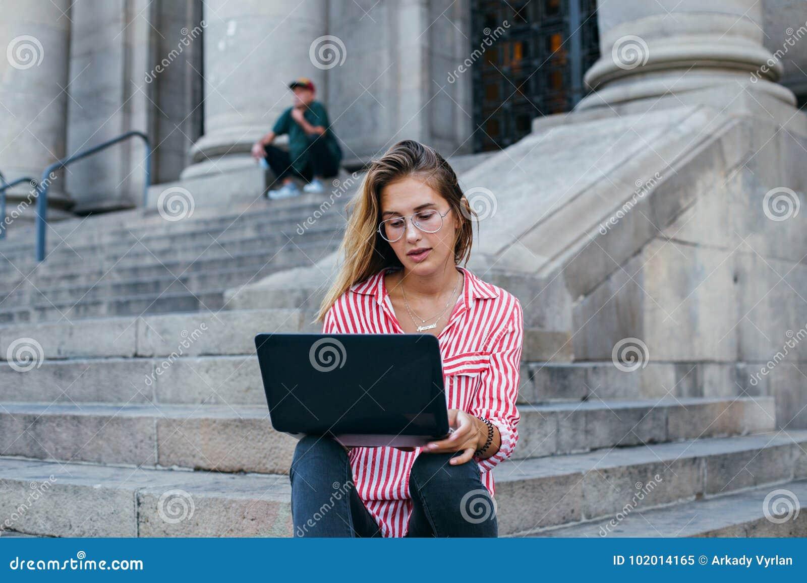 Entzückender hübscher Student sitzt auf Treppe mit Laptop