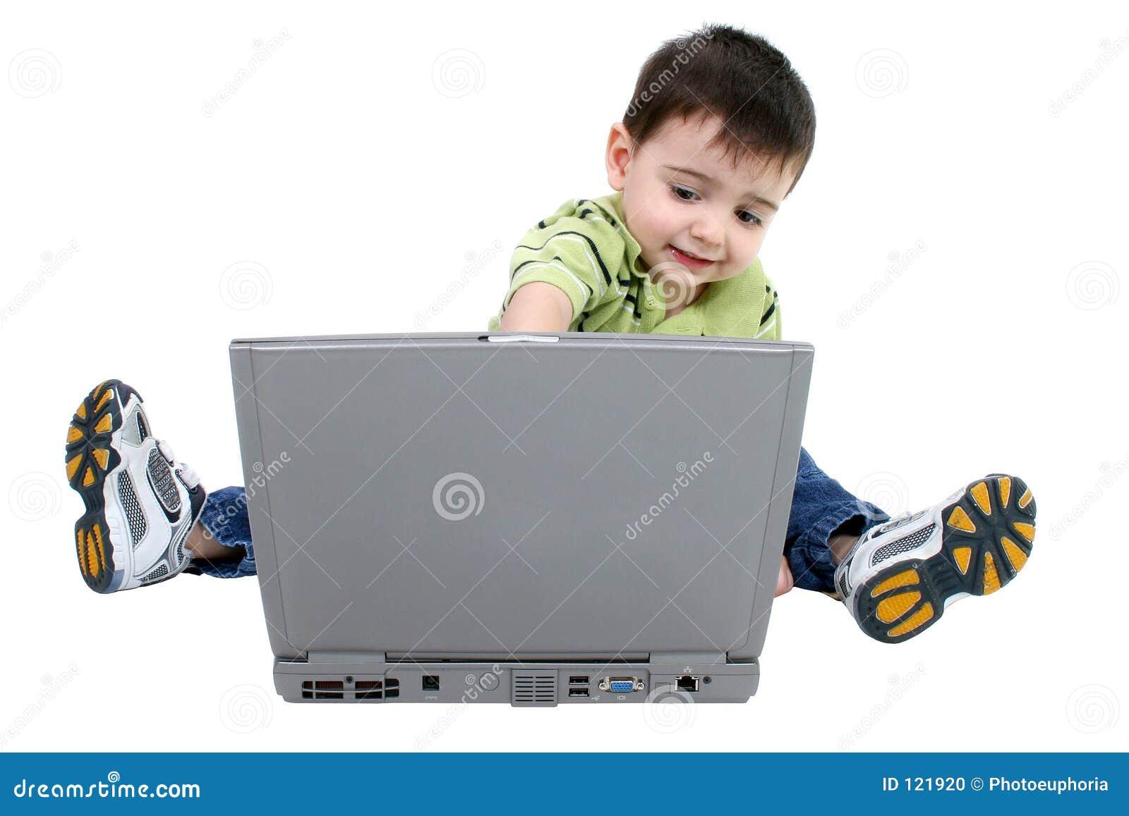 Entzückender Junge, der an Laptop über Weiß arbeitet