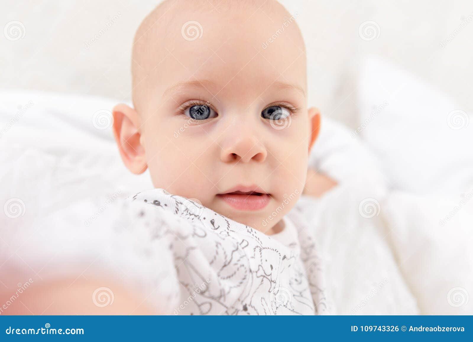 Entzückendes Baby mit den blauen Augen, die direkt der Kamera versucht, für sie zu erreichen betrachten Netter Kleinkindabschluß