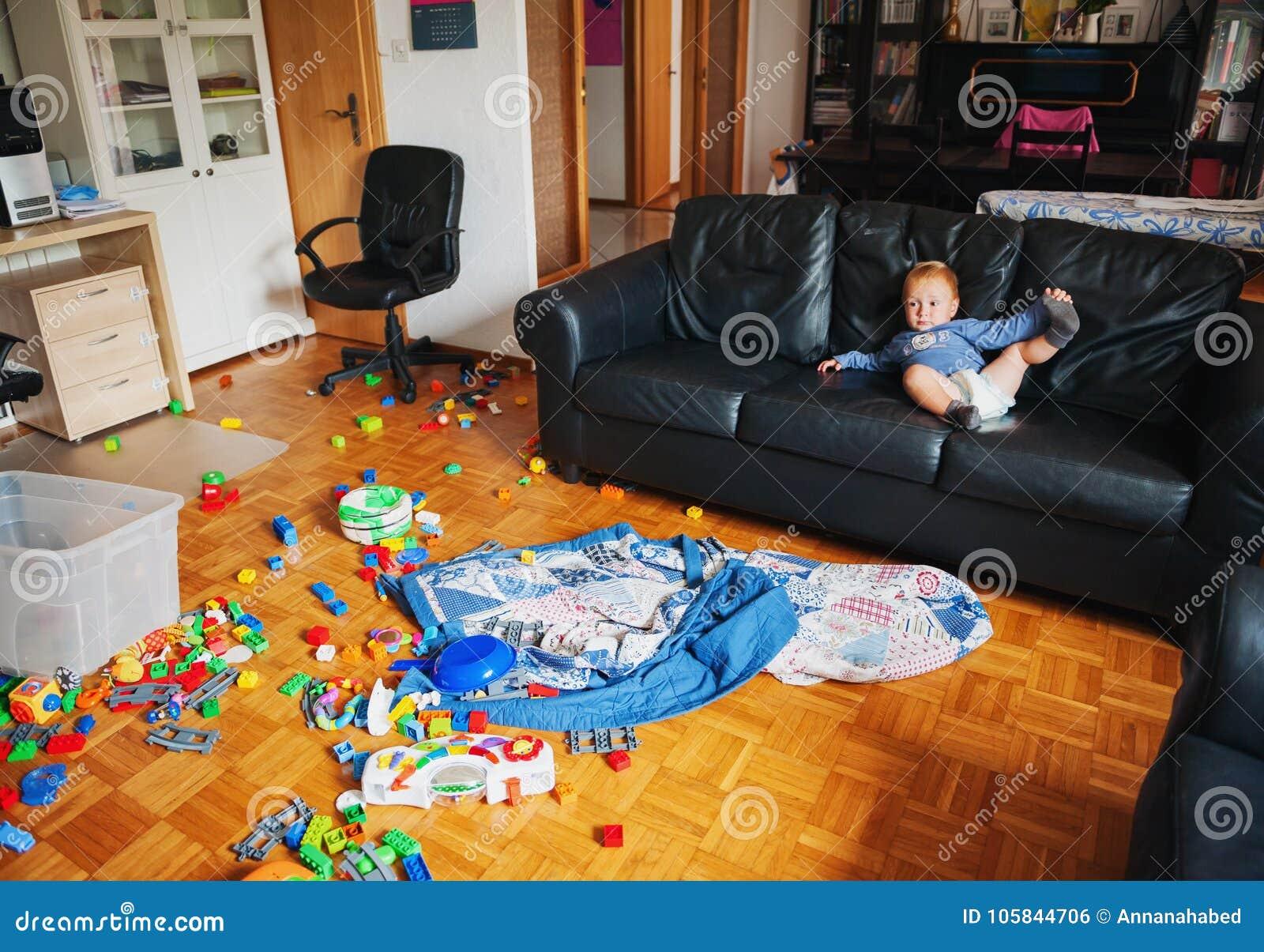 Entzückendes einjähriges Baby mit dem lustigen Gesichtsausdruck, der in einem sehr unordentlichen Wohnzimmer spielt