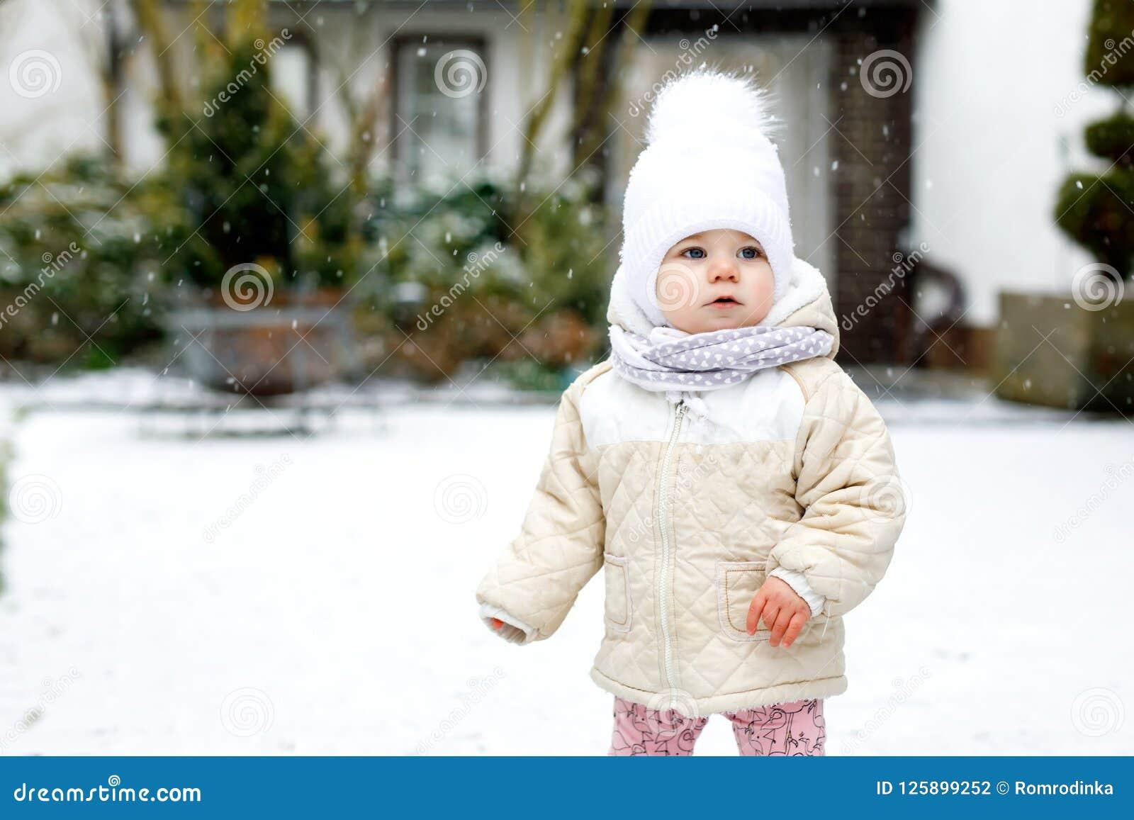 Entzückendes kleines Baby, das draußen erste Schritte im Winter macht Nettes Kleinkind, welches das Gehen lernt Kind, das Spaß au
