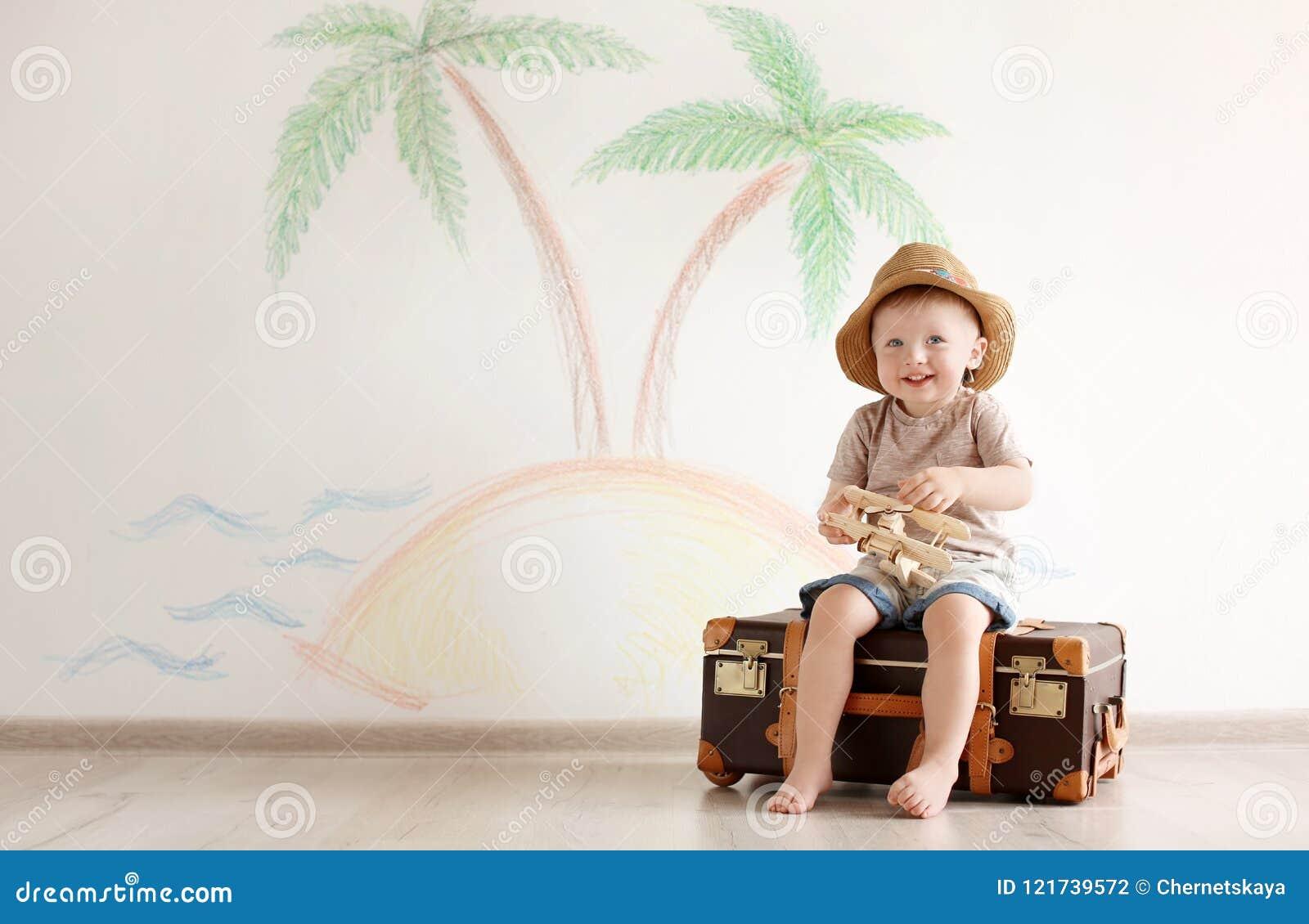 Entzückendes kleines Kind, das Reisenden mit Koffer spielt