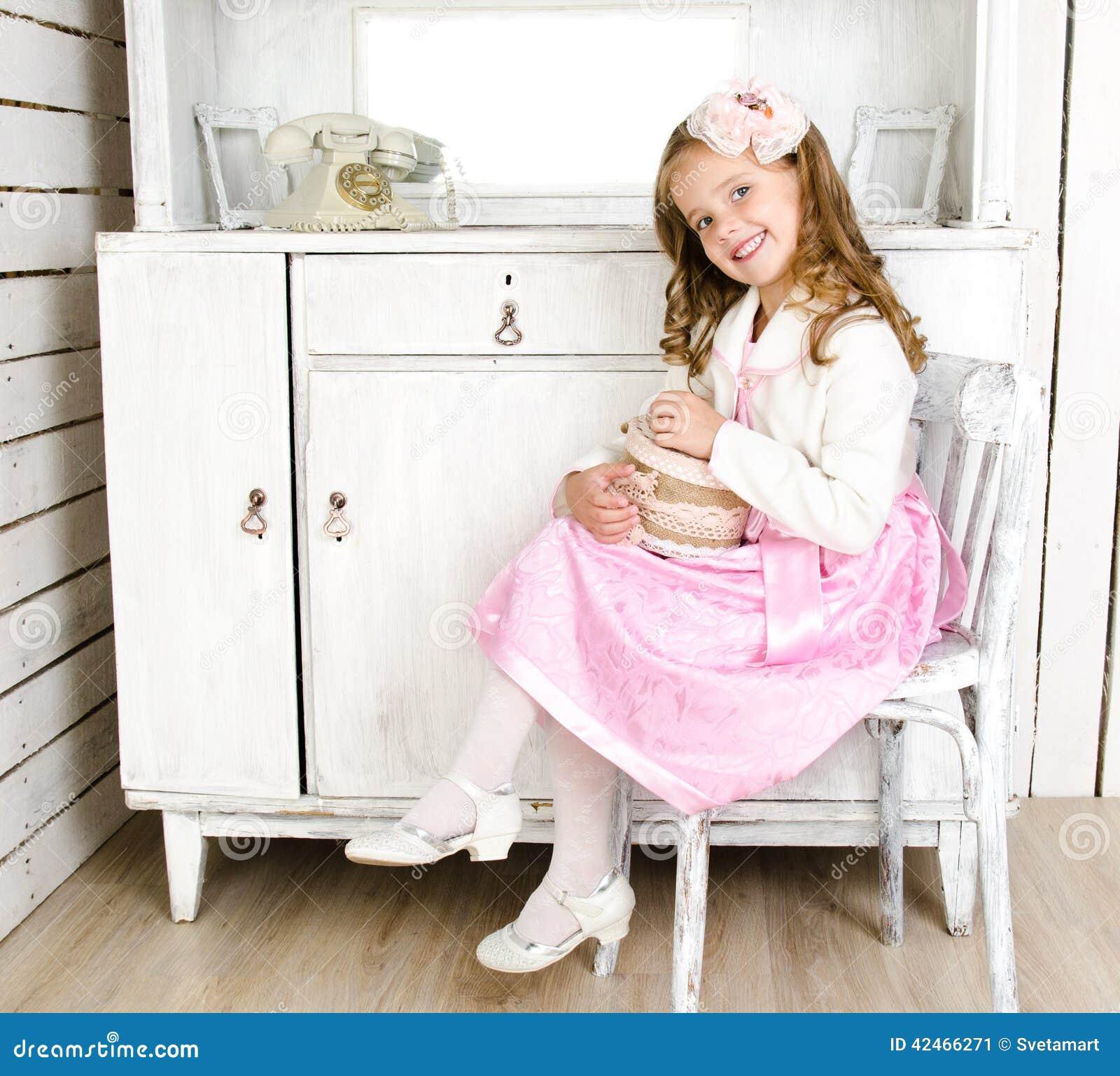 Entzückendes kleines Mädchen, das auf Stuhl mit Geschenkbox sitzt