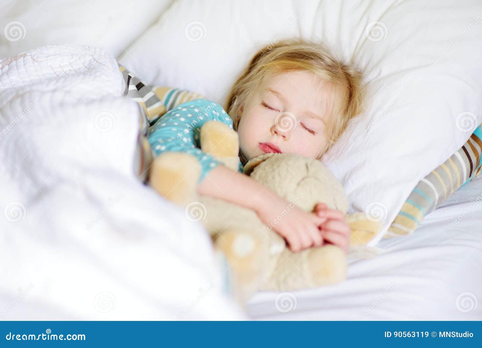 Entzückendes kleines Mädchen, das im Bett mit ihrem Spielzeug schläft