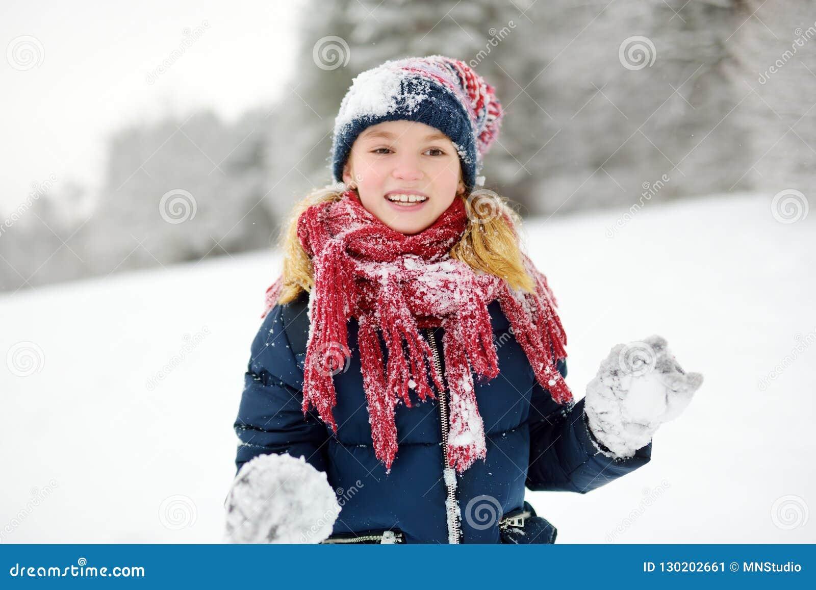 Entzückendes kleines Mädchen, das Spaß im schönen Winterpark hat Nettes Kind, das in einem Schnee spielt