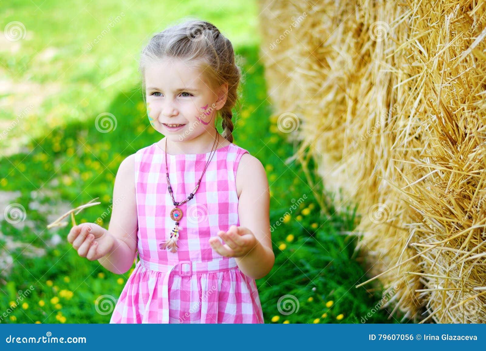 Entzückendes kleines Mädchen nahe einem Heuschober am sonnigen Sommertag