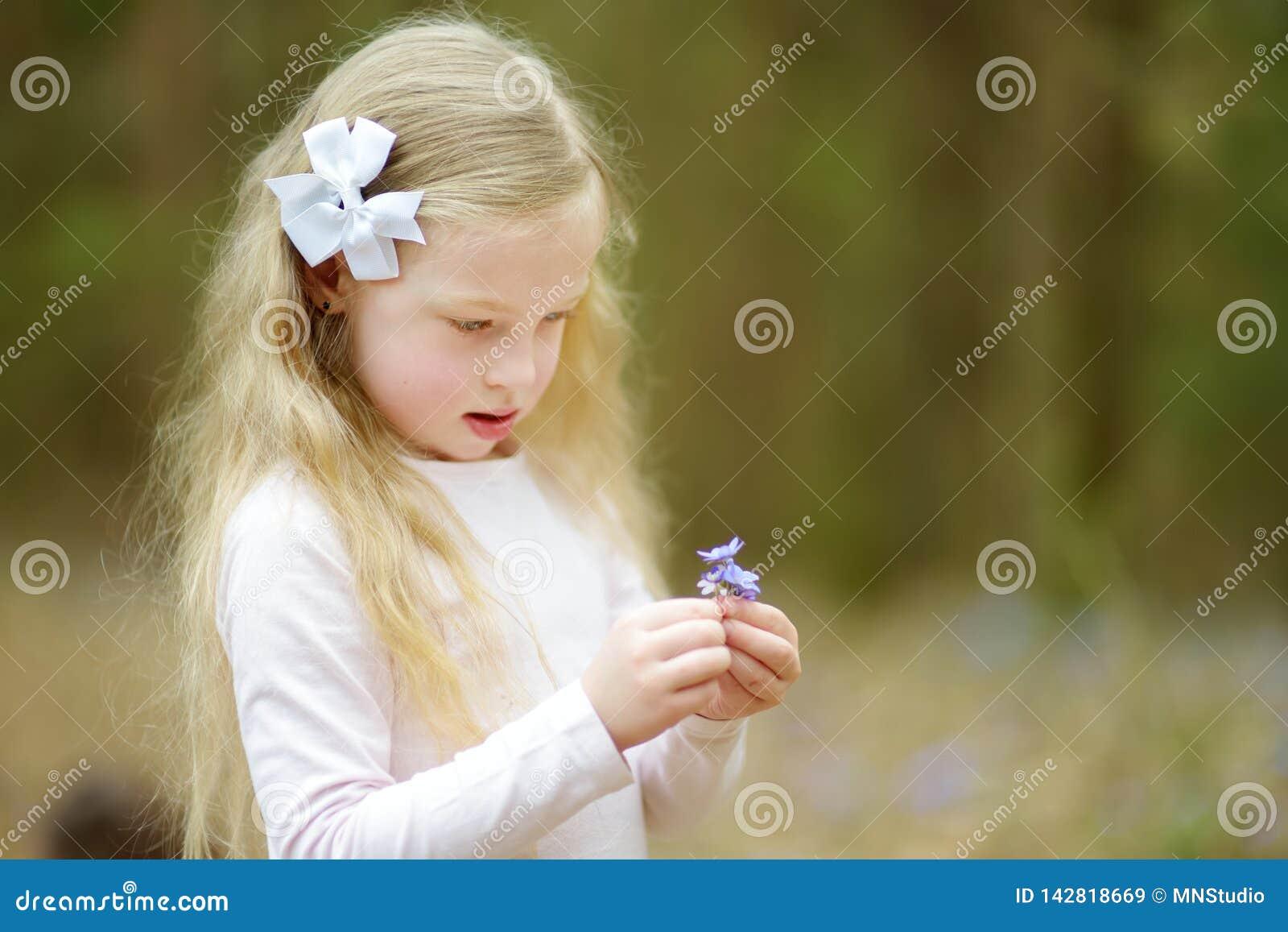 Entzückendes kleines Mädchen, welches im Wald die ersten Blumen des Frühlinges am schönen sonnigen Frühlingstag auswählt