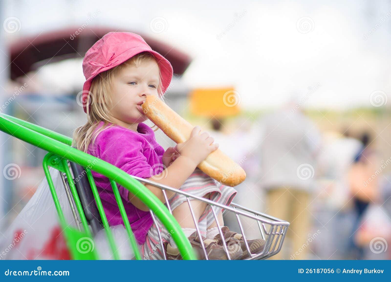 Entzückendes Schätzchen essen langes Brot, sitzen im Wagen