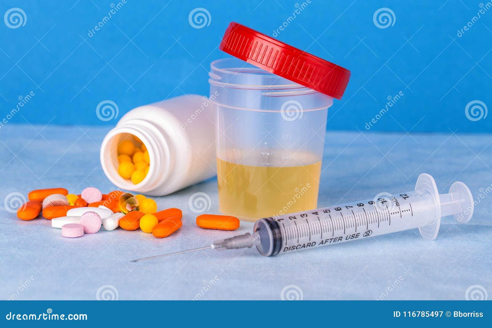 Envase de la orina, jeringuilla y píldoras coloreadas