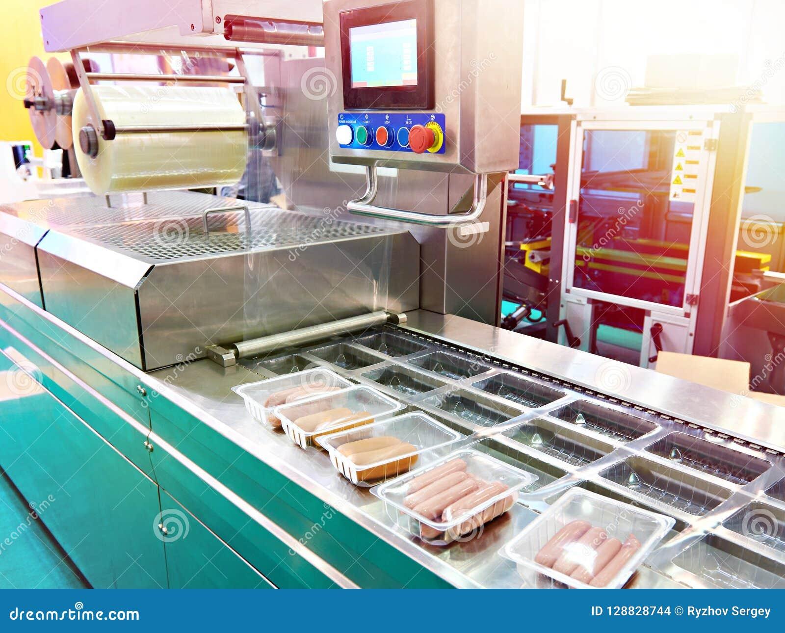 Envases de plástico con las salchichas en transportador en la fábrica de la comida