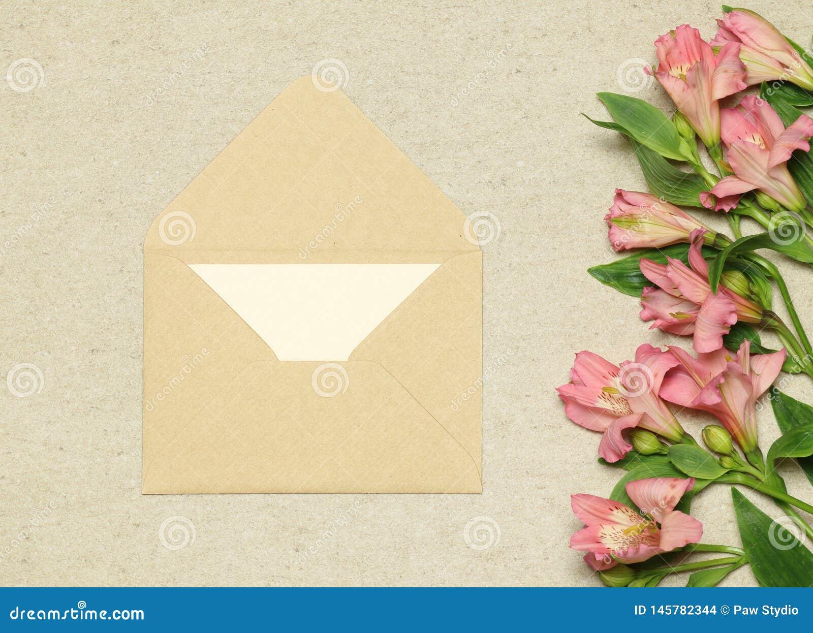 Envelope bege do ofício com papel e flores no fundo de pedra