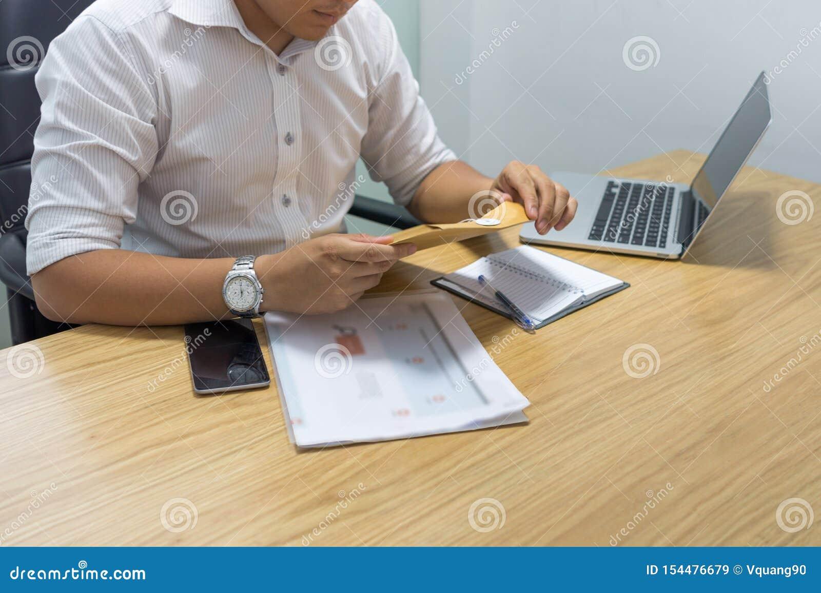 Envelope da abertura da mão do homem de negócios no escritório