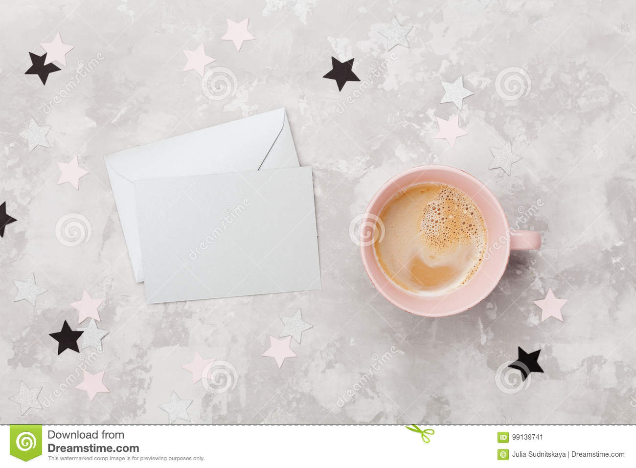 Envelope with empty card and cup of coffee on womans working desk top view. Flat lay. Party invitation or greeting message.
