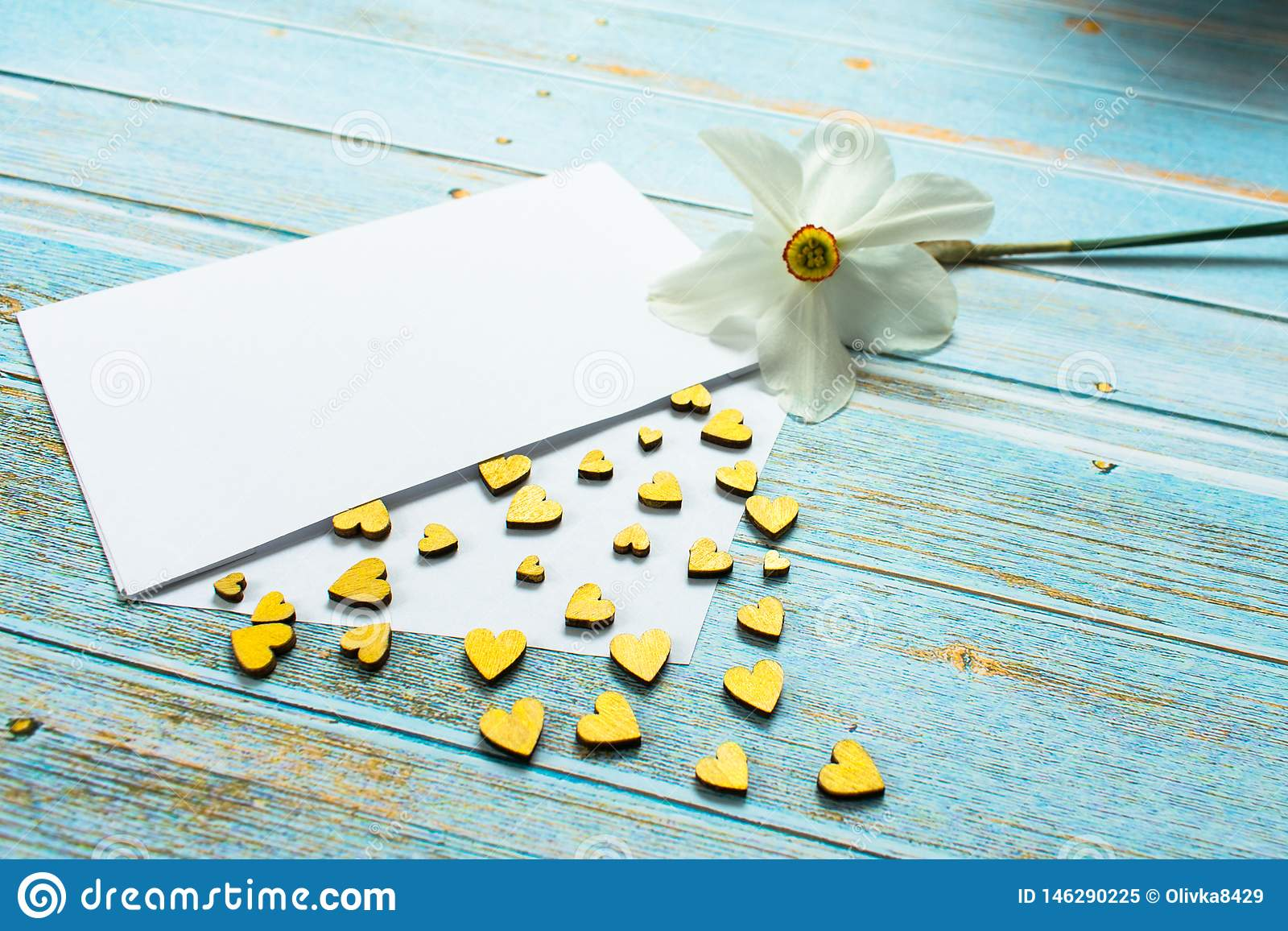 Envelope with golden hearts and a flower daffodil flower on the table. Mothers Day. Valentine`s Day. Love concept. Gift, message f