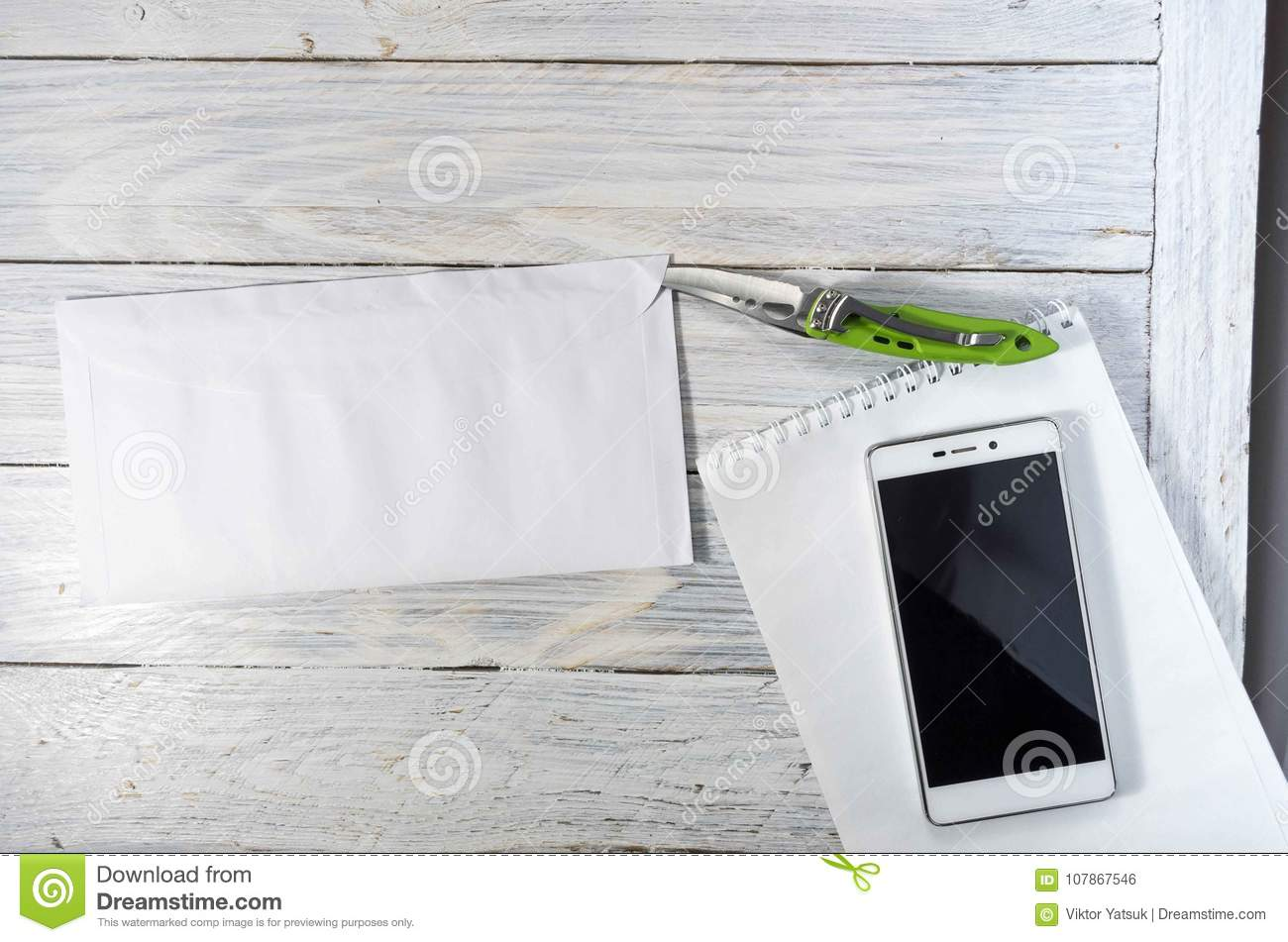 Envelope With A Letter On The Desktop  Knife, Notebook And Mobile