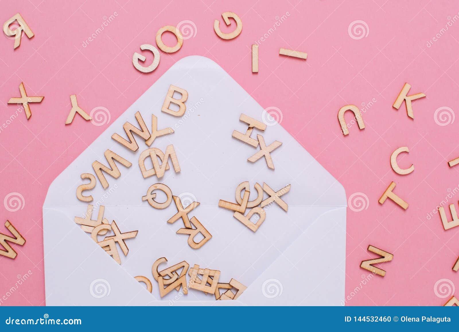 Enveloppe blanche ouverte avec beaucoup de lettres d ABC sur le fond rose