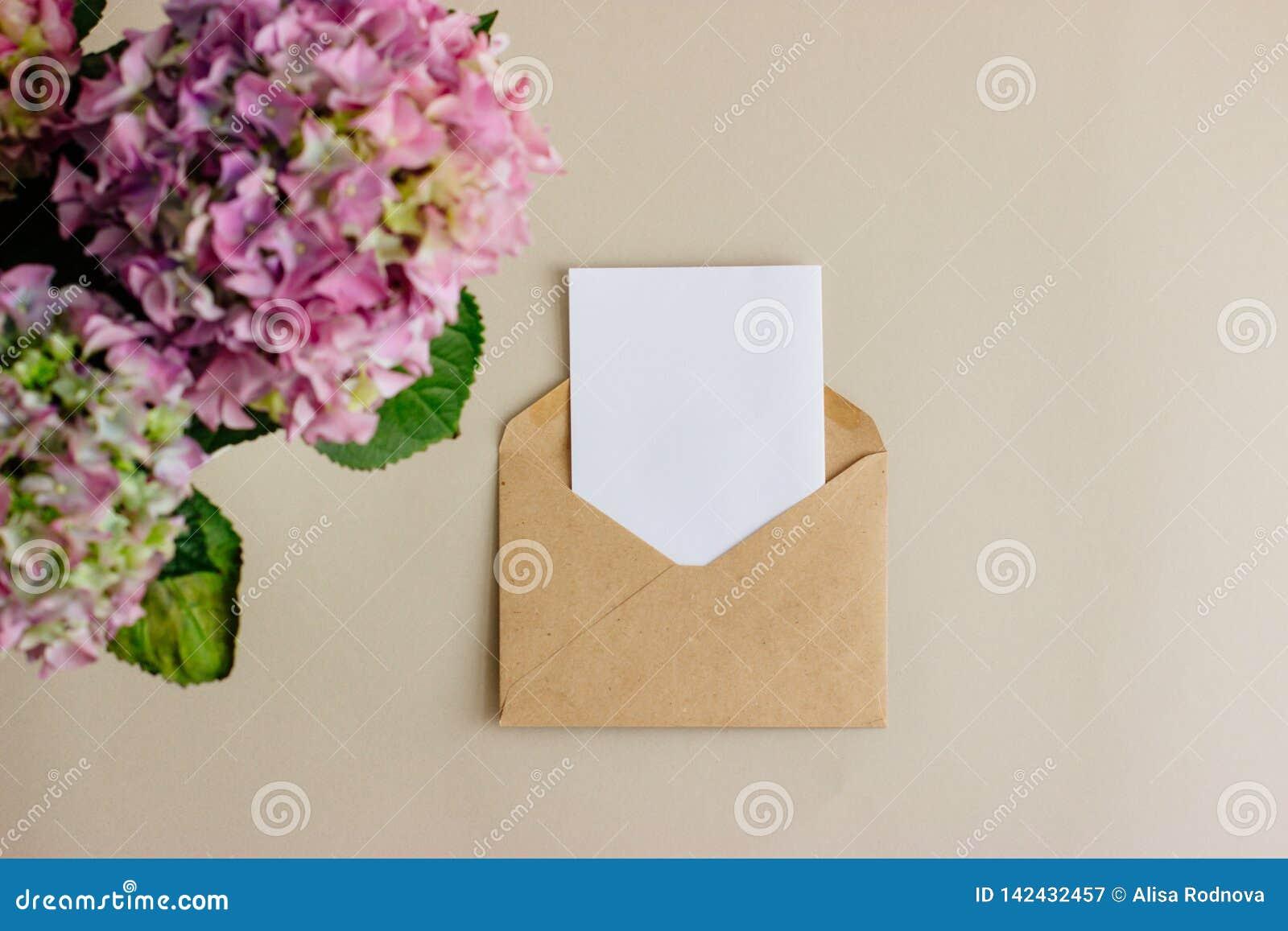 Enveloppe de papier d emballage avec la carte blanche sur le fond clair