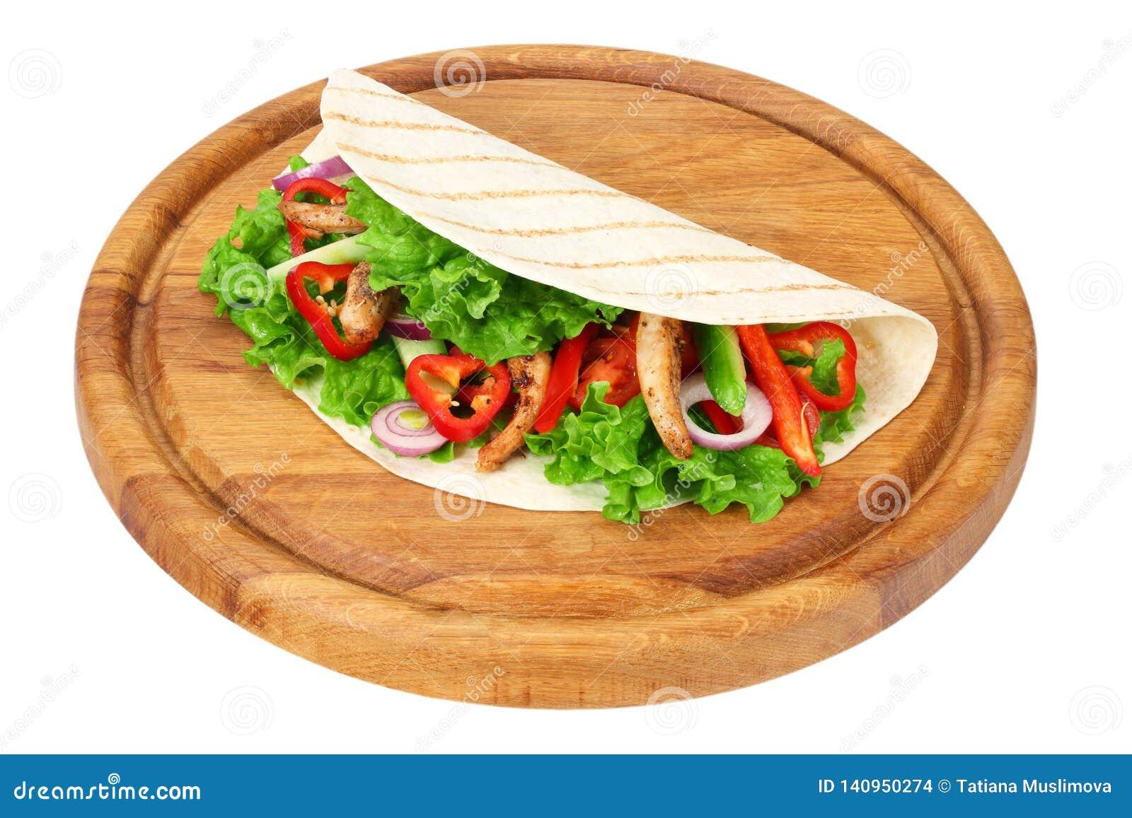 Enveloppe de tortilla avec de la viande et des légumes de poulet frit sur le conseil en bois d isolement sur le fond blanc