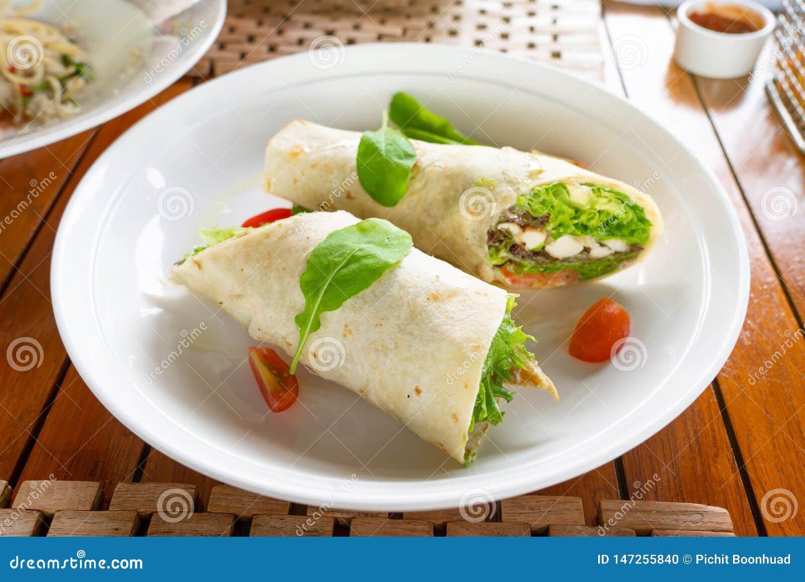 Enveloppe de tortilla avec de la viande et des l?gumes de poulet sur le plat traditionnel toping avec des ?pinards