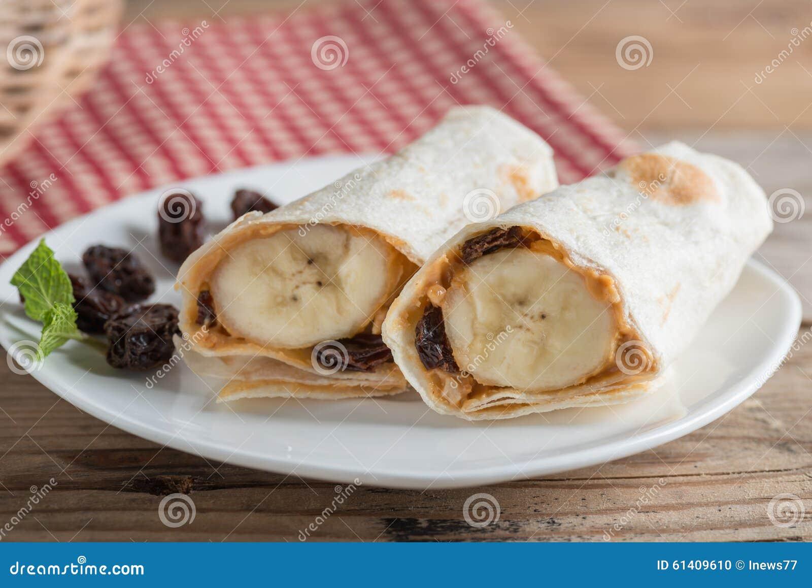 Enveloppe de tortilla avec le beurre, le raisin sec et la banane d arachide
