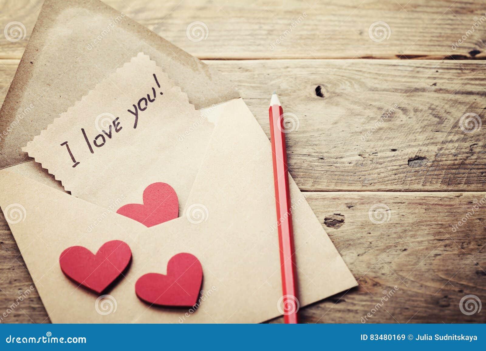enveloppe ou lettre  coeurs rouges et notes je t u0026 39 aime sur la table en bois rustique pour le jour