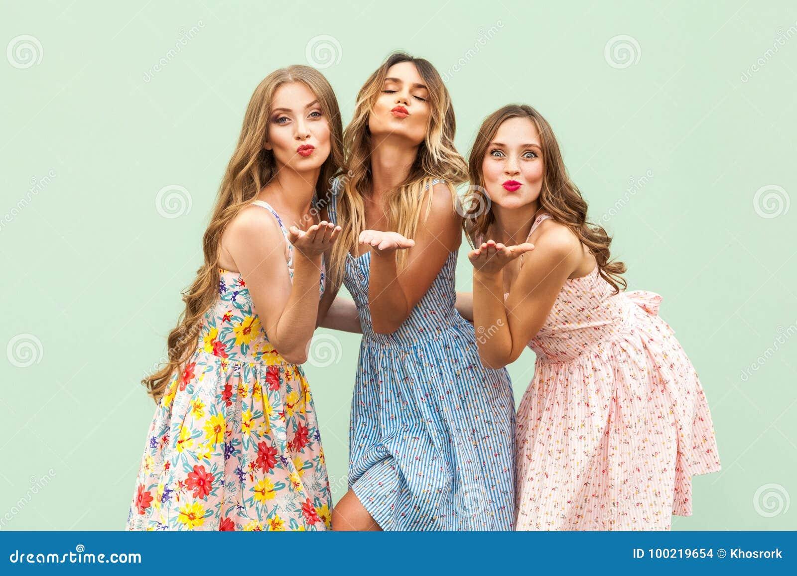 Enviando o beijo do ar Três melhores amigos que levantam no estúdio, vestido vestindo do estilo do verão contra o fundo verde