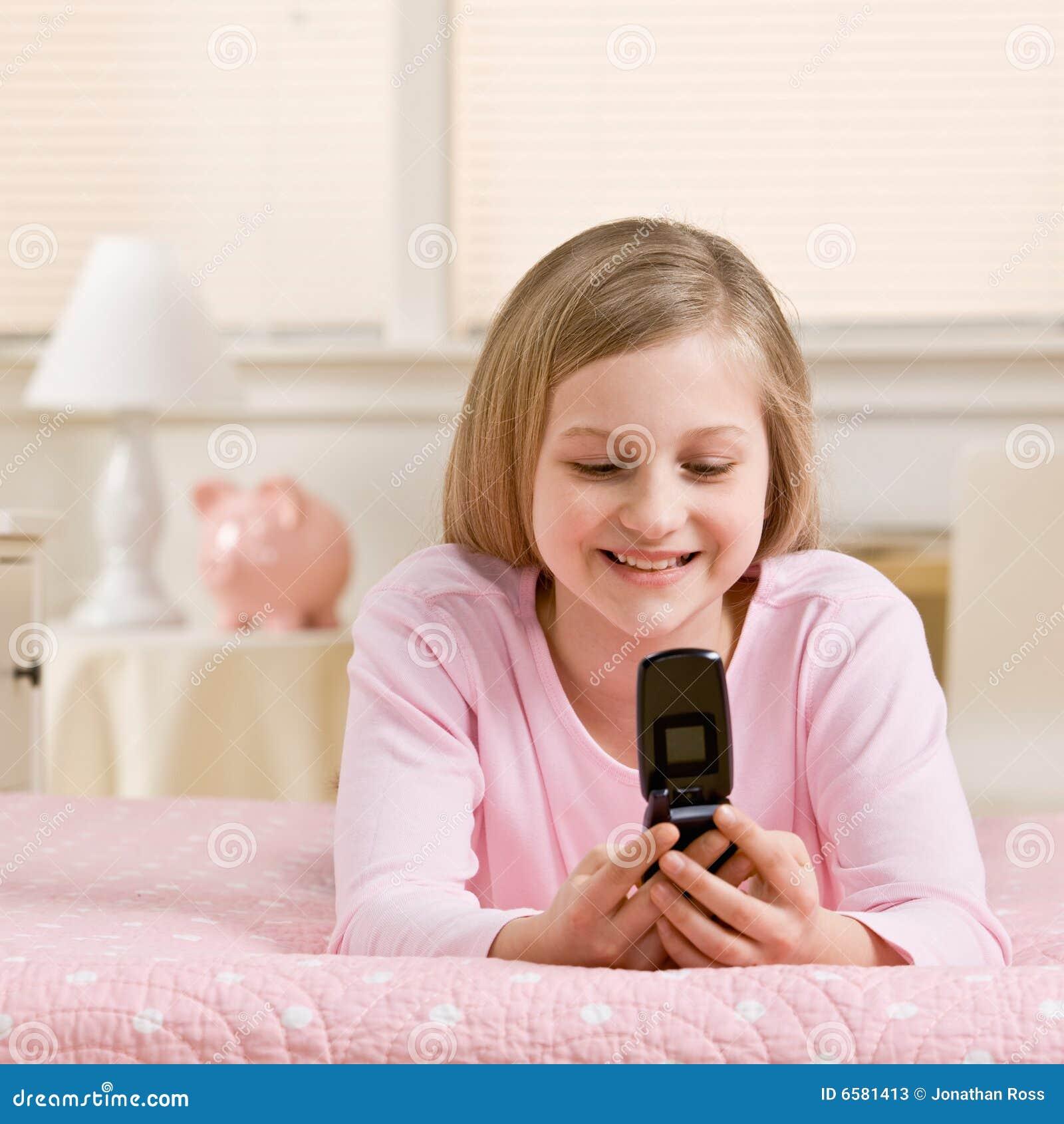 Envio de mensagem de texto da menina no telefone de pilha em seu quarto