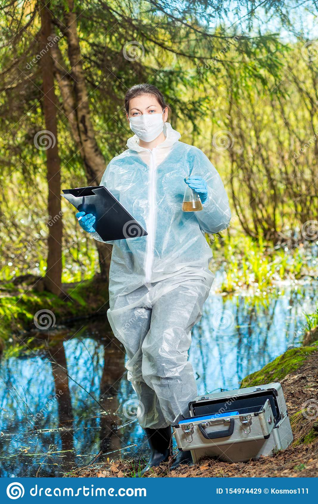 environmentalist biologist in the forest takes water samples