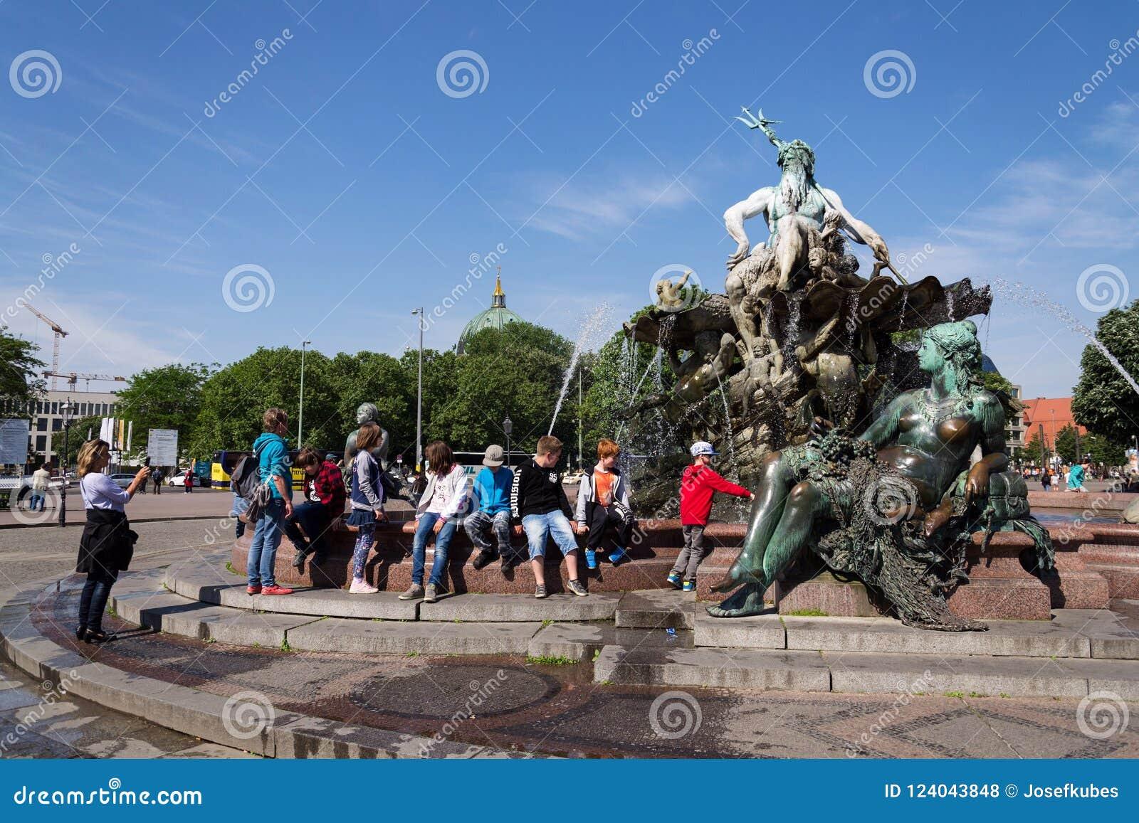 Eople framme av Neptunspringbrunnen - Neptunbrunnen med den grekiska guden Poseidon och kvinnastatyer i Berlin, Tyskland