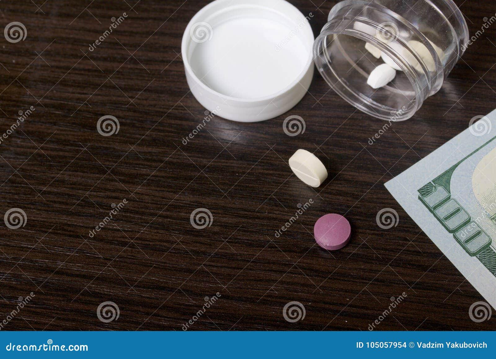 A epidemia das drogas As tabuletas estão em um recipiente plástico claro com a tampa removida Mentira de diversas tabuletas na ta