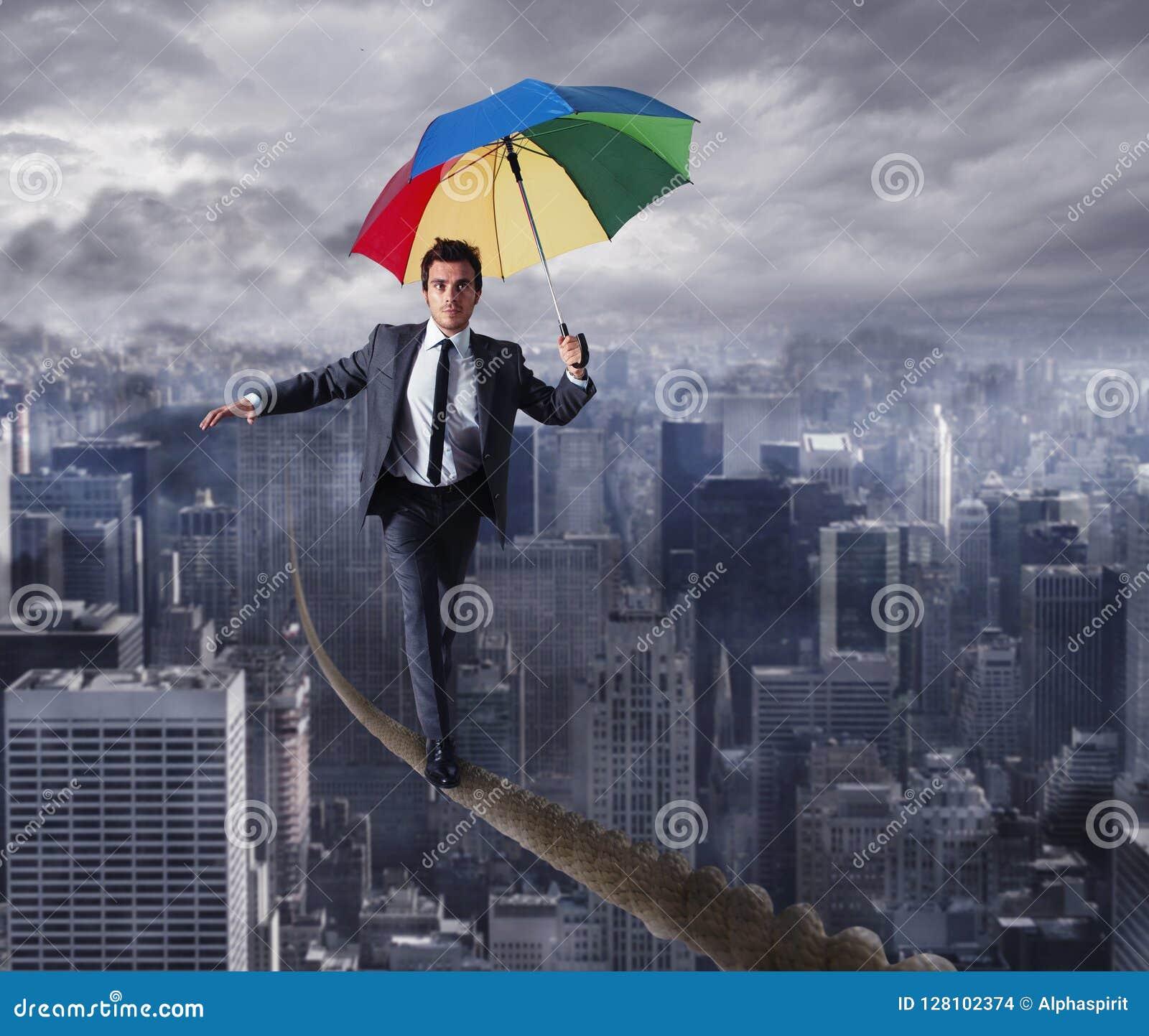 Equilibrist在一条绳索的商人步行与在城市的伞 概念克服问题和阳