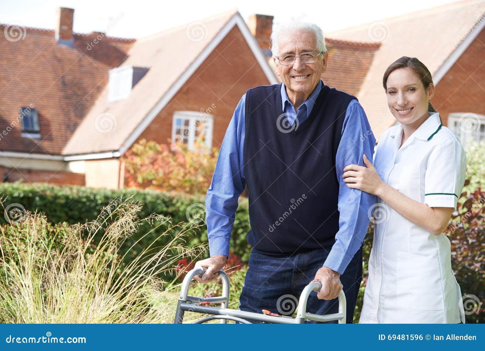 Equipa de tratamento que ajuda o homem superior a andar no jardim usando o quadro de passeio