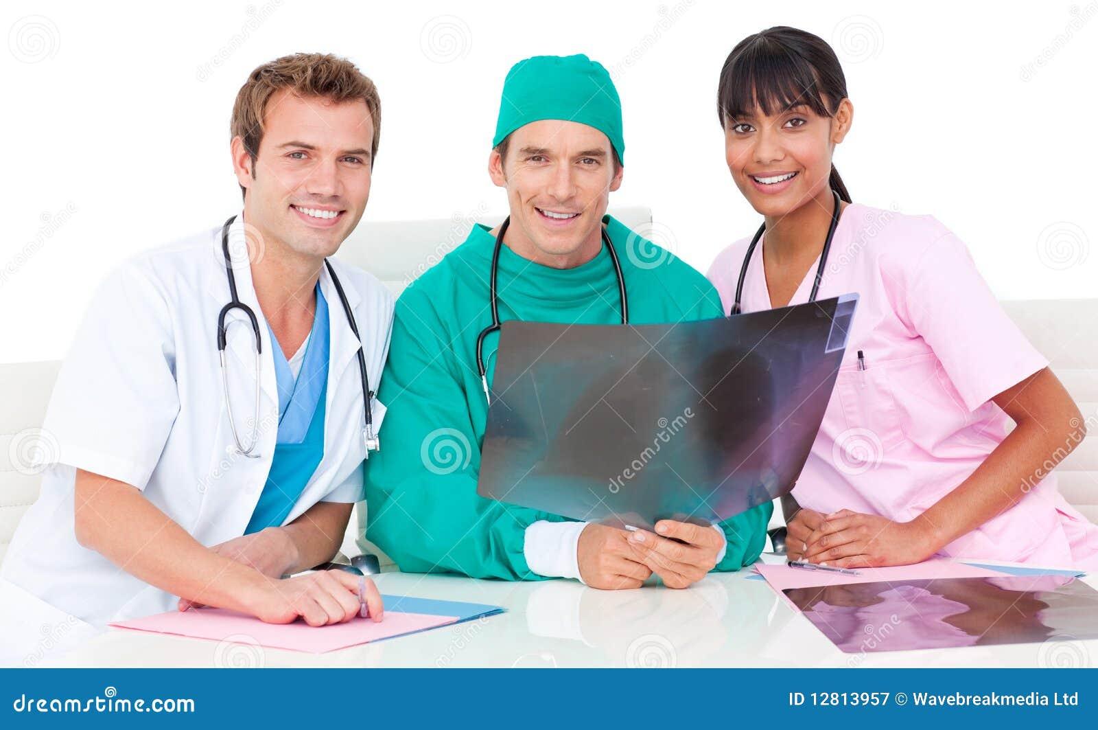 Equipa médica de sorriso que olha o raio X