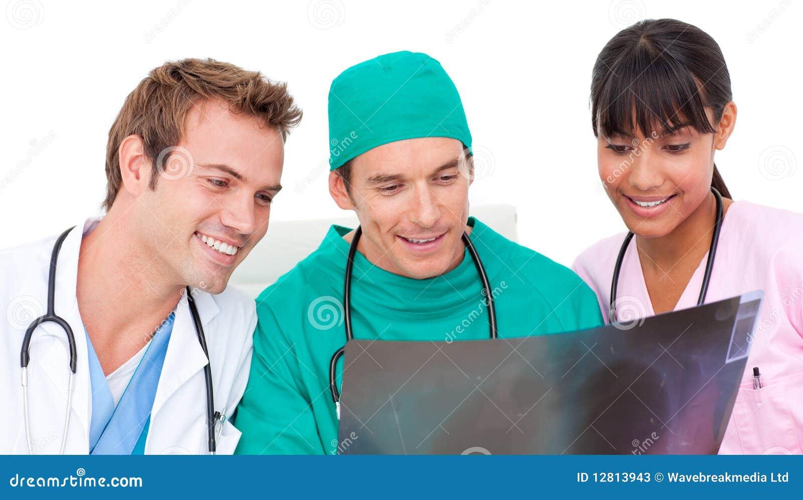 Equipa médica entusiástica que olha o raio X